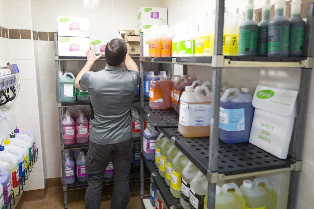 Employee checks chemical stock on shelf